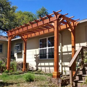 "Garden Pergola (Options: 6' L x 16' W, Redwood, No Electrical Wiring Trim, Open Roof with Slats at 18"", Rafters at 18"", 4-Post Anchor Kit, No Ceiling Fan Base, No Privacy Panels, No Curtain Rods, 9' Post Height, Transparent Premium Sealant). Photo Courtesy of L. Manning of Boeme, TX."