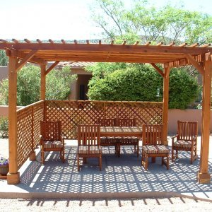 "Garden Pergola (Options: 15' x 15', Redwood, No Electrical Wiring Trim, Lattice Panel Roof, 4-post Anchor Kit for Stone, No Ceiling Fan Base, 2 Privacy Panels, No Curtain Rods, 9' Post Height, Transparent Premium Sealant). Under the Pergola, a 7' San Francisco Patio Table Set with 42"" W Tabletop, 4 Ruth Chairs and 2 Ruth Armchairs. Photo Courtesy of Mr. Joseph Dlugosz of Sedona, AZ."