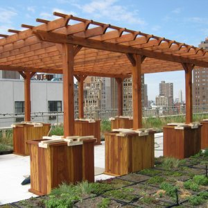"Typical Roof Top Installation: Garden Pergola (Options: 26' L x 18' W, Mature Redwood, No Electrical Wiring Trim, Rafters at 18"" and Slats at 18"", Lengthwise Roof Support Timbers, 6-Post Anchor Kit for Stone, No Ceiling Fan Base, No Privacy Panels, No Curtain Rods, 9' Post Height, Transparent Premium Sealant). Custom Request: 2 Extra Post. No leak roof installation using planters with concrete. NYC skyline in background."