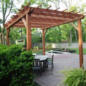 "Garden Pergola (Options: 16' L x 12' W, Mature Redwood, No Electrical Wiring Trim, Open Roof with Slats at 18"", Rafters at 18"", Lengthwise Roof Support Timbers, 4-Post Anchor Kit for Stone, No Ceiling Fan Base, No Privacy Panels, No Curtain Rods, 9' Post Height, Transparent Premium Sealant)."