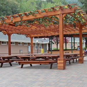 "Garden Pergola (Options: 30' L x 30' W, Redwood, No Electrical Wiring Trim, Open Roof with Slats at 18"", Rafters at 18"", 6-Post Anchor Kit for Gale-Wind, No Ceiling Fan Base, No Privacy Panels, No Curtain Rods, 10' Post Height, Transparent Premium Sealant). After the tables and pavers were added. Picnic Tables are not Forever Redwood Tables. Photo Courtesy of Via West Campground located at 13851 Stevens Canyon Rd, Cupertino, CA."