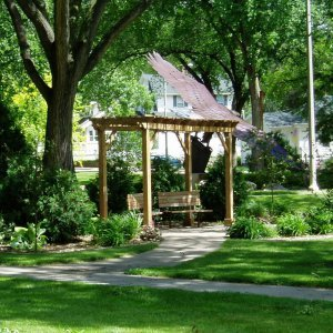 "The Peace Place in memory of Joshua at Custer Park, downtown Bismarck by Paula Nordwall. Garden Pergola (Options: 16' L x 8' W, Douglas-fir, No Electrical Wiring Trim, Open Roof with Slats at 18"", Rafters at 18"", Lengthwise Roof Support Timbers, 4-Post Anchor Kit for Stone, No Ceiling Fan Base, No Privacy Panels, No Curtain Rods, 9' Post Height, Transparent Premium Sealant)."